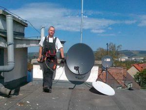 Montaż anten - serwisant na dachu przy antenie